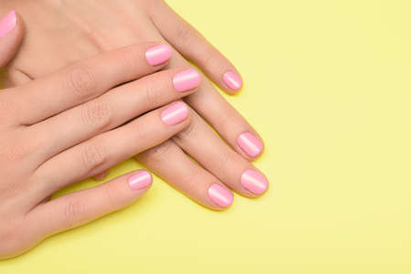 Female hands with pink nail design. Pink nail polish manicured hands. Female hands on yellow background