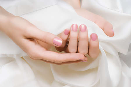 Female hands with pink nail design. Pink nail polish manicured hands. Woman hands hold white fabric 免版税图像