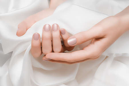 Female hands with pale pink nail design. Pale pink nail polish manicured hands. Woman hands hold white fabric 免版税图像