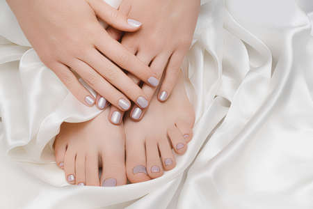 Female hands and feets with silver nail design. Silver nail polish manicure and pedicure on white fabric