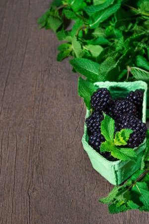 Ripe blackberry berries. Green paper basket with blackberry. Blackberry and mint leafs 免版税图像