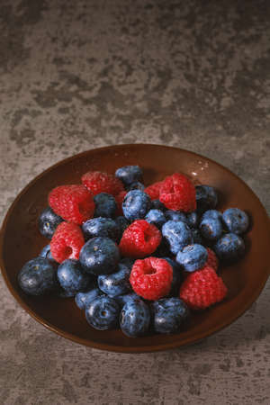 Blueberry and raspberry in a clay plate. Raw berries mix close up. Summer fresh berries