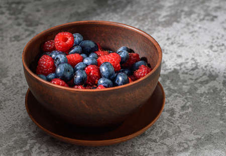 Blueberry and raspberry in a clay plate. Raw berries mix close up 免版税图像