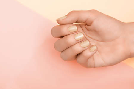 Female hand with yellow nail design. Yellow nail polish manicure. Female hands on pale yellow background