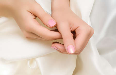 Female hands with pink nail design. Pink nail polish manicured hands. Woman hands on white fabric background