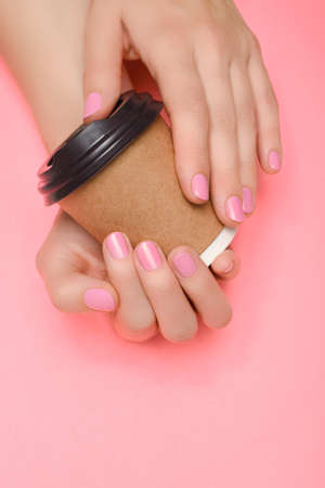 Female hands with pink nail design. Pink nail polish manicure. Coffee cup in female hands on pink background