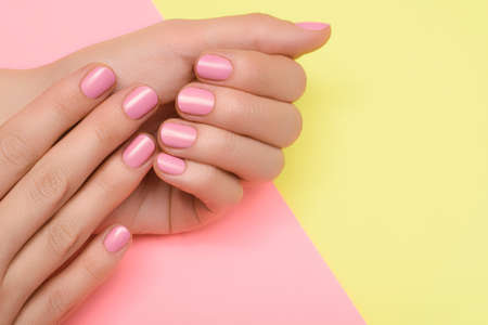 Female hands with pink nail design. Pink nail polish manicure. Female hands on yellow pink background