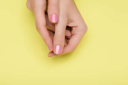 Female hands with pink nail design. Pink nail polish manicure. Female hands on yellow background