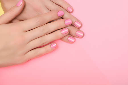 Female hands with pink nail design. Pink nail polish manicure. Female hands on pink background