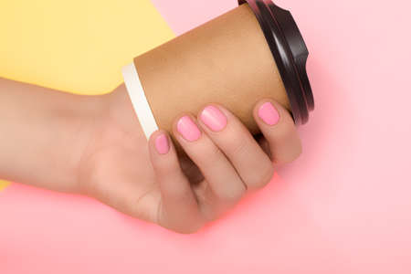 Female hands with pink nail design. Pink nail polish manicure. Coffee cup in female hands on yellow pink background