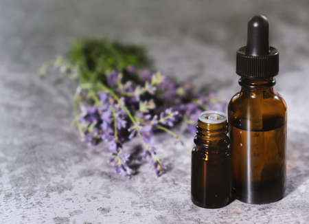 Lavender essential oils. Lavender flowers on stone desk. Medical essential oil bottles