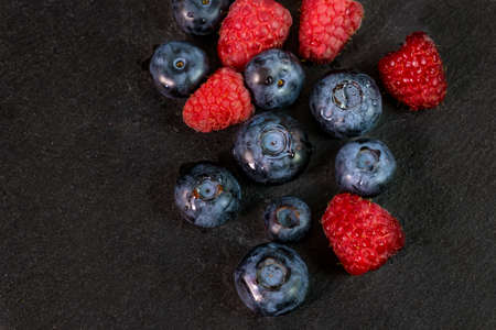 Blueberry and raspberry isolated on black background. Raw berries mix isolated