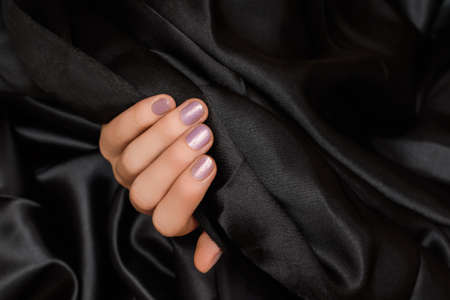 Female hand with pink nail design. Pink nail polish manicure. Woman hand hold black fabric 免版税图像