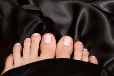 Female feets with white nail polish. Woman legs with white nail design on black fabric