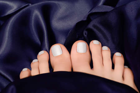 Female feets with white nail polish. Woman legs with white nail design on blue fabric