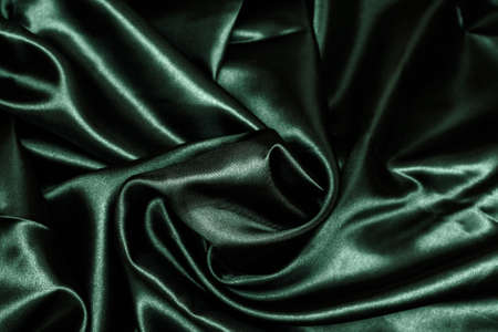 Shiny green fabric. Green wavy fabric background