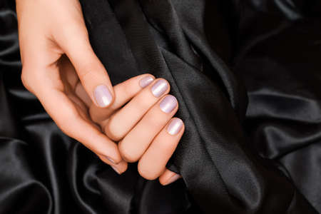 Female hands with pink nail design. Pink nail polish manicure. Woman hands hold black fabric