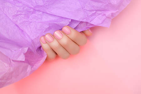 Female hand with pale pink nail design. Pale pink nail polish manicure. Female hands hold pale pink crumpled paper.
