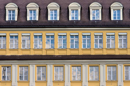 mansard: Facade with rows of windows.Mansard roof and yellow facade in typical german architecture style building. Munich,Bavaria,Germany