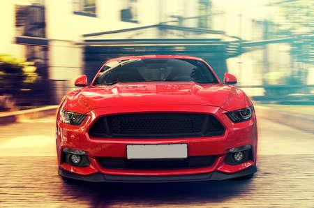 赤いスポーツカー。アメリカのレーシングカーは前線都市背景のビューを閉じます。