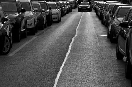 car lots: Cars parked on the roadside.Black and white urban image of a row of parked cars. Busy street with lots of traffic.