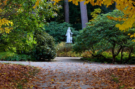falla: Staue autumn in a park in fall.A beautiful garden statue of a woman in Botanical garden near Nymphenburg during. Munich, Germany Stock Photo