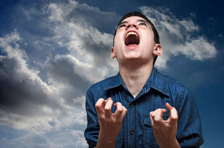 Boy screaming.Angry caucasian teenager screaming wildly on a cloudy sky background.