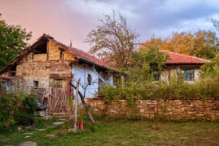 Backyard of typical old Bulgarian house in a village. Courtyard of old balkan house in northern Bulgaria during sunset, traditional eastern European countryside. Stock Photo