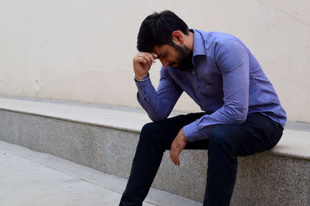 Stressed and sad young man sitting outside holding head with a hand looking down. Human emotion feelings, sad bearded man Banque d'images
