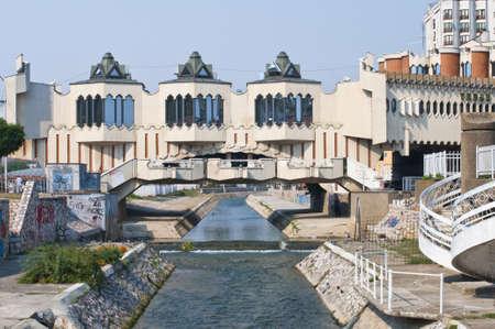 ノヴィ ・ パザル市内中心部。歩道橋の建物と都市チャネル。