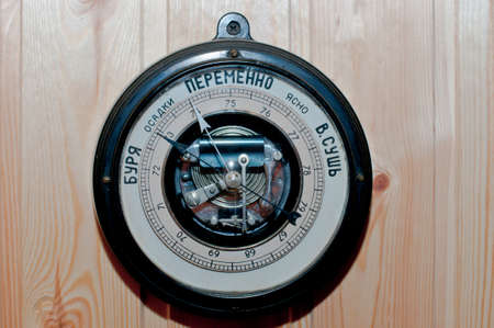 aneroid: Old black barometer with russian letters on the wooden wall Stock Photo