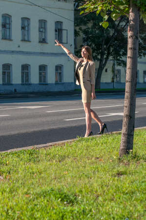hailing: Business woman catches a Taxi in the street of Moscow
