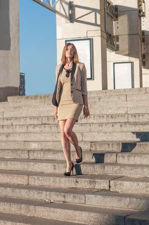 bajando escaleras: Joven y atractiva mujer de negocios está bajando en las escaleras