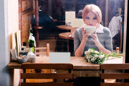 woman with cup of coffee in grey suit behind cafe window photo