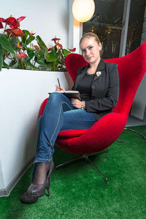 Secretary girl in office with red chair and red flowers photo