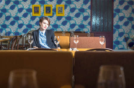 Brunet girl is sitting in interior of Moscow restaurant Golubka. photo