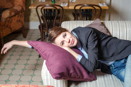 Brunet girl is on the sofa in interior of Moscow restaurant Golubka. photo