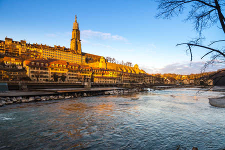 Bern cathedral at Aare shore in golden hour photo