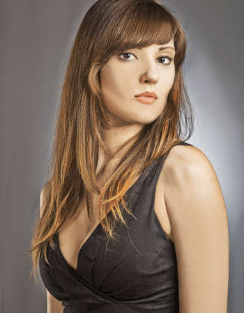 supercilious: Young woman with long brown hairs in black dress Stock Photo