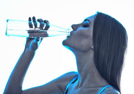 Young woman is trinking water from glass bottle photo