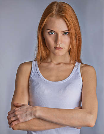 Young attractive woman with reddish (carrot colored) hair in relaxed pose, gray background.
