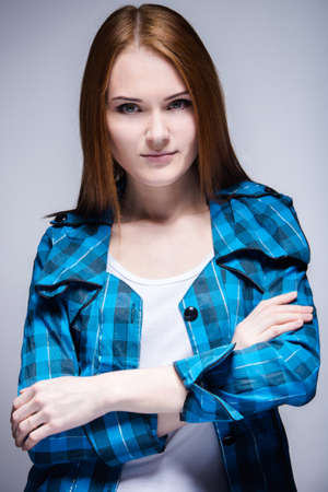 Young attractive woman with reddish hair in relaxed pose, gray background.