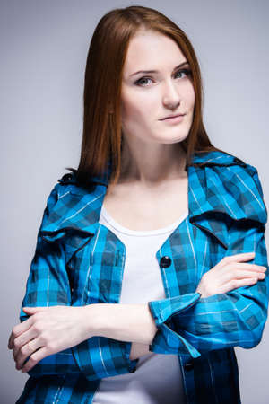 underskirt: Young attractive woman with reddish hair in relaxed pose, gray background.