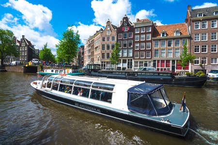 enclosed: AMSTERDAM, NETHERLANDS - 11 May 2014 A glass enclosed tourist boat on a canal on 11 May 2014, Amsterdam, Netherlands. Editorial