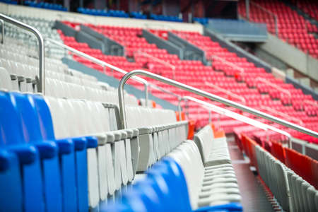 aisles: Row of empty red, white and blue chairs in a sporting stadium. Stock Photo