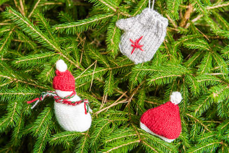 Knitted Chrismas toys on green fir branches photo