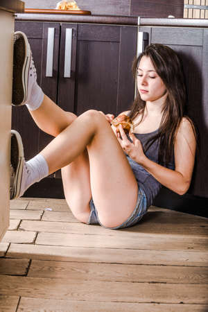 Girl is sitting on floor in the kitchen