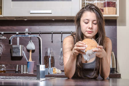 tedium: Teenaged girl is eating burger in kitchen interior