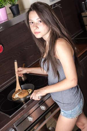 cabizbajo: Chica cocina est� calentando hamburguesa en pan Foto de archivo