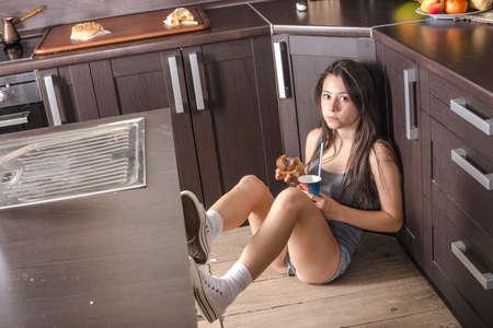 cabizbajo: La muchacha está sentada en el suelo en la cocina Foto de archivo
